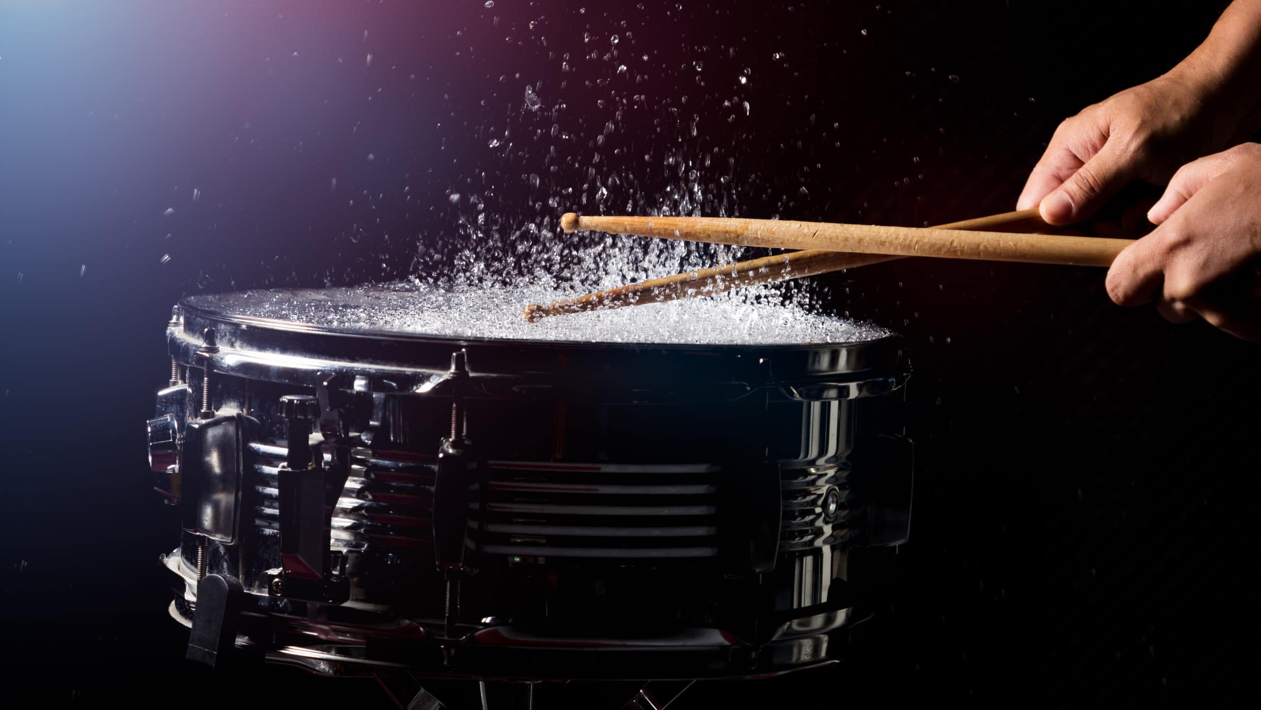 The drum sticks are hitting on the snare drum with splash water in low light background